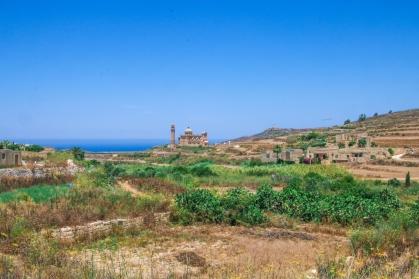 Vy över landsbygd med kyrka i horisonten.